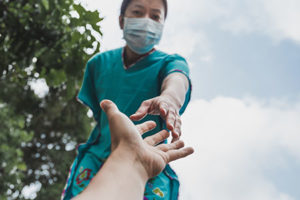 Woman with protective maks reaching out her hand to help during outbreak coronavirus